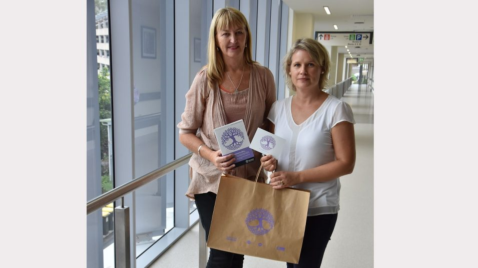 Social worker Nola Powell and project officer Wendy Pearse with the handover bags, card and booklet.